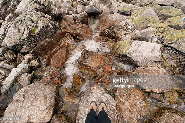 Close up of a mountain river flowing with female hiking boots in High Tatra Mountains, Poland.