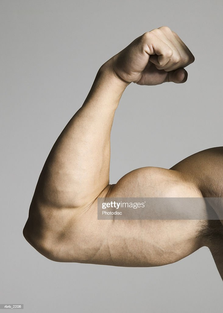 close up of a muscular male arm as he flexes his biceps : Foto de stock