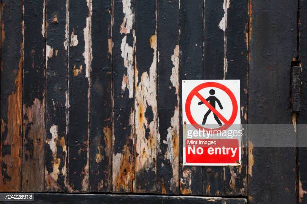 Close up of a No Entry sign on a weathered wooden wall.