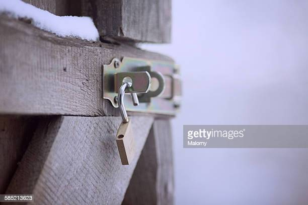 Close up of a padlock on an open wooden door