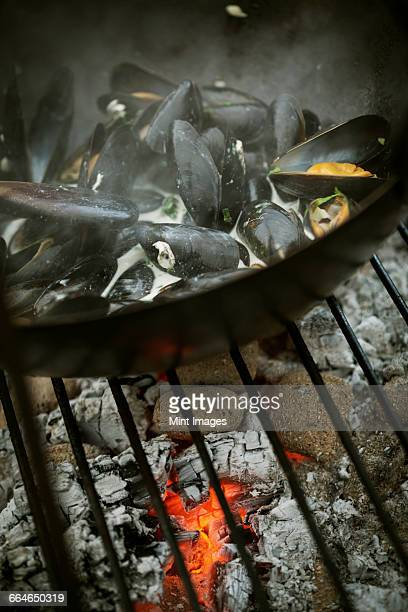Close up of a pan of Black Mussels over a charcoal barbecue.