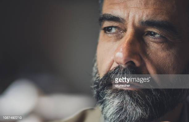 close up of a pensive mature man looking away. - introspection stock pictures, royalty-free photos & images
