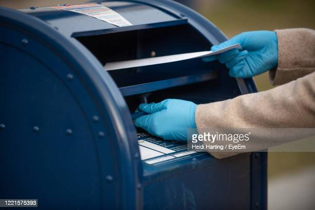 close up of a person mailing a letter - glove stock pictures, royalty-free photos & images