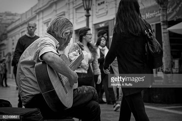 Close up of a person playing guitar profile view of the pedestrian city of Cordoba Argentina on the afternoon of October 31 2014