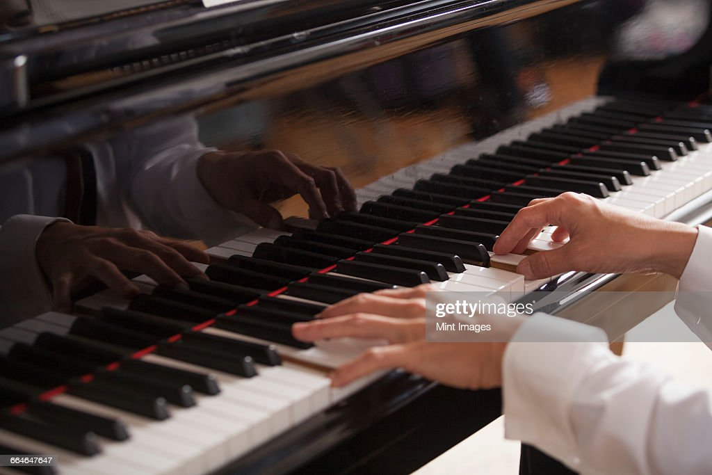 Close up of a pianists hands, playing on a grand piano. : ストックフォト