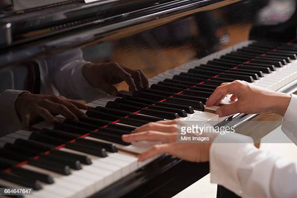 Close up of a pianists hands, playing on a grand piano.