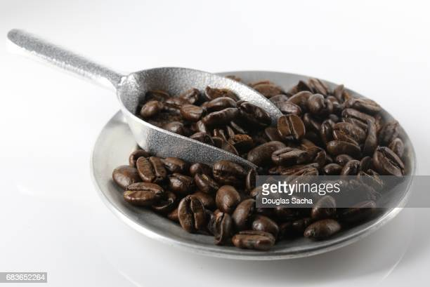 Close up of a pile of roasted Coffee beans on a white background