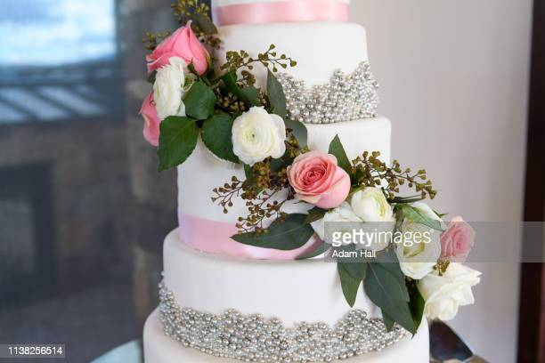 close up of a pink and white roses flowers on a wedding cake with leaves, beads and ribbon - utah wedding stock pictures, royalty-free photos & images