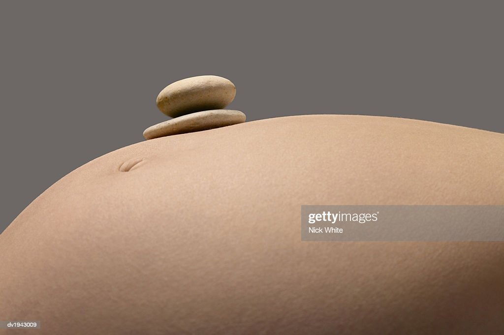 Close up of a Pregnant Woman's Stomach With Two Pebbles on Top of it : Stock Photo