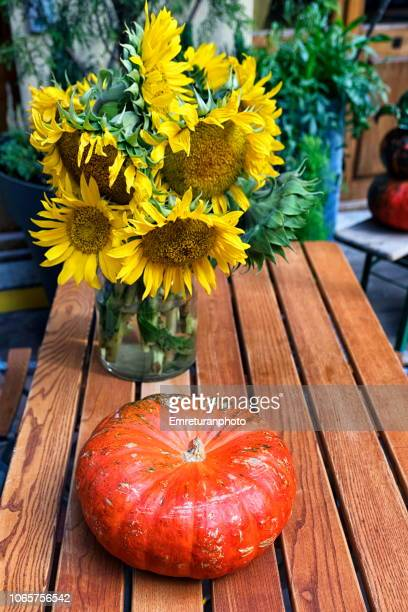 Close up of a pumpkin and sunflowers in a vase on a wooden table..