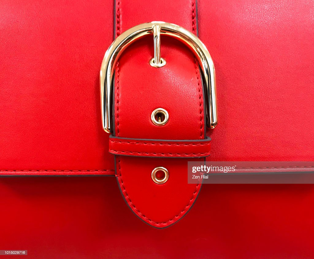 Close up of a red purse detail showing belt buckle design on flap : Stock Photo