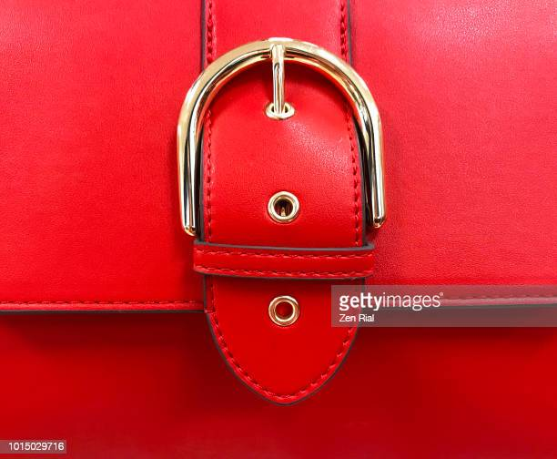 close up of a red purse detail showing belt buckle design on flap - red belt stock photos and pictures