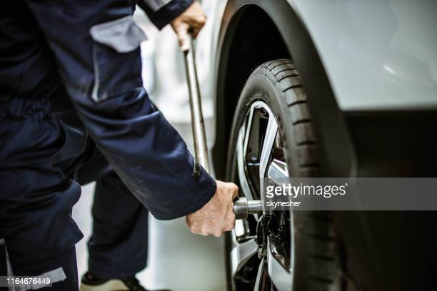close up of a repairman changing wheel and tire in a workshop. - tighten stock pictures, royalty-free photos & images
