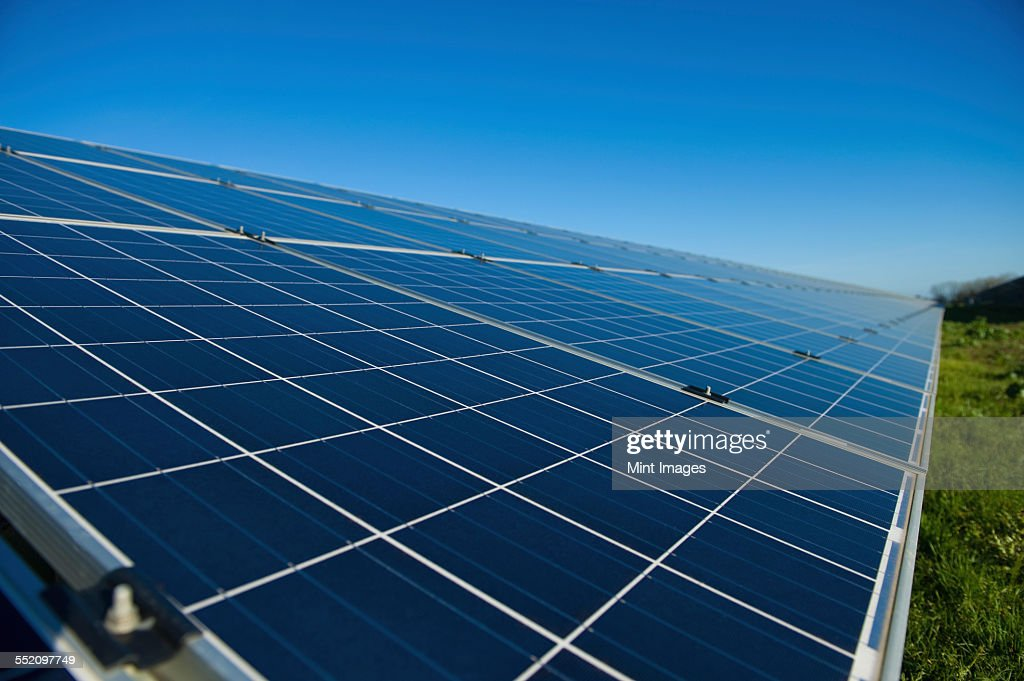 Close up of a row of solar panels in an open field. A solar farm. : Stock Photo