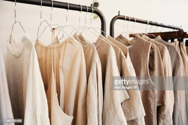close up of a selection of clothes in natural colours on a rail in a boutique. - modieus stockfoto's en -beelden