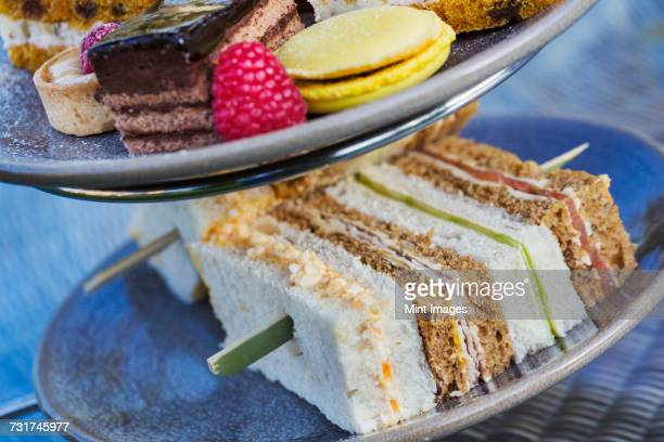 Close up of a selection of sandwiches and cakes, traditional afternoon tea.
