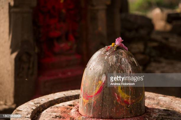 close up of a shiva lingam with kumkum and offerings of flowers in the hindu temple area alongside the river in the hanuman ghat area of bhaktapur in the kathmandu valley, nepal. - shiva lingam stock pictures, royalty-free photos & images