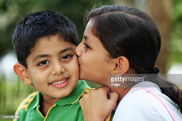 Close up of a sister kissing her brother