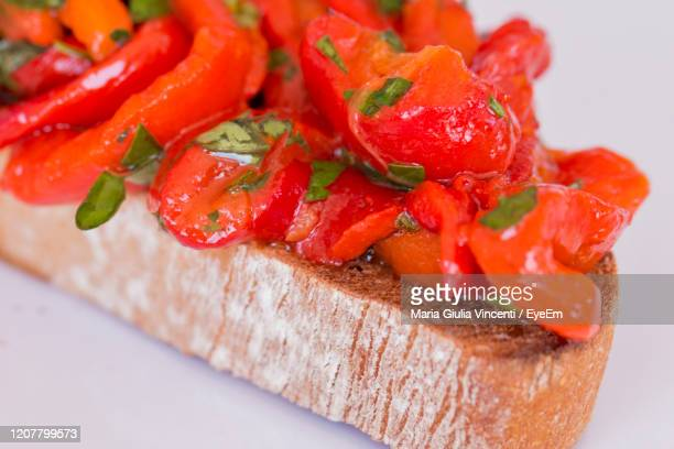 close up of a slice of bruschetta with red sweet filleted peppers. - maria giulia vincenti foto e immagini stock