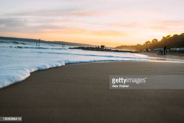 close up of a small wave on sandy beach at sunset - プール湾 ストックフォトと画像