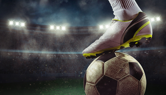 Close up of a soccer striker ready to kicks the ball at the stadium 1164702658