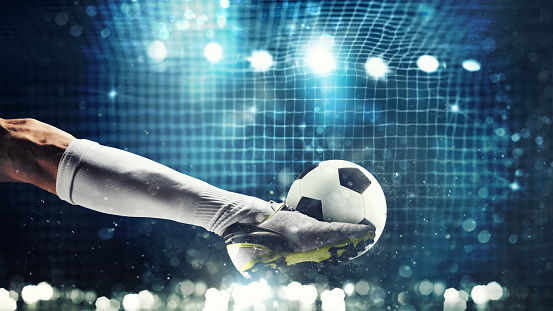 Close up of a soccer striker ready to kicks the ball in the football goal 982766506