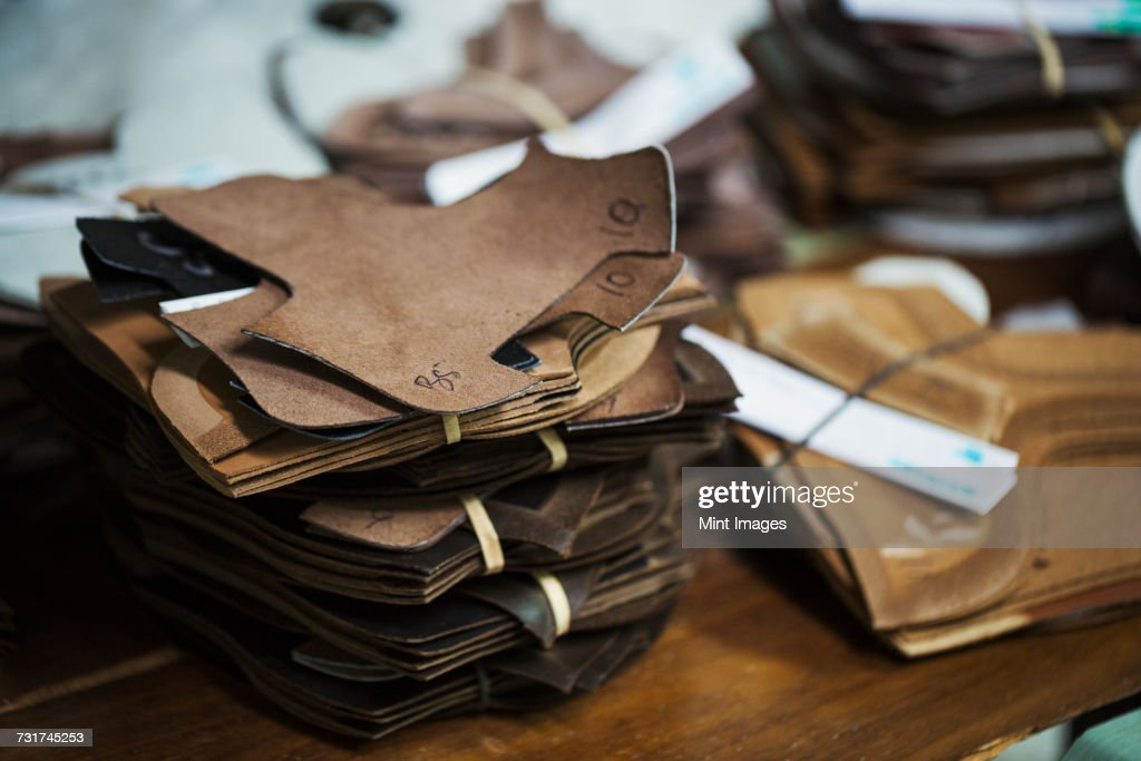 Close up of a stack of brown leather pieces in a shoemakers workshop. : Stock Photo