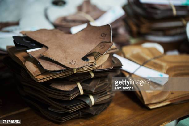 close up of a stack of brown leather pieces in a shoemakers workshop. - brown shoe stock pictures, royalty-free photos & images