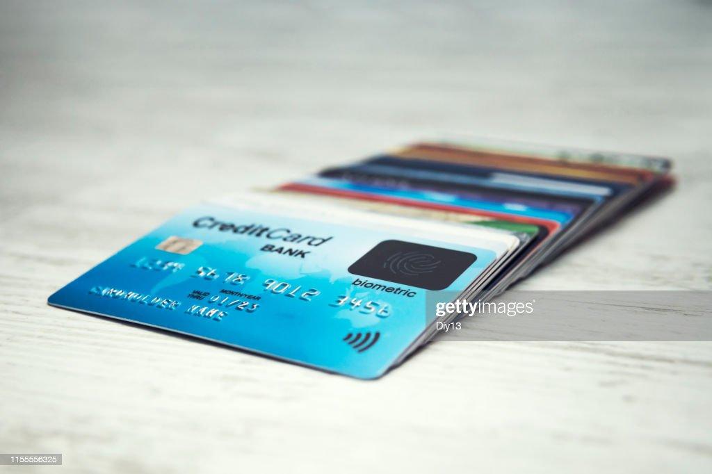 クレジットカードのスタックのクローズアップは、白いテーブルの上に順番に横たわっています。バイオメトリックカードの上に多くの異なるクレジットカード。バイオメトリックスキャン� : ストックフォト