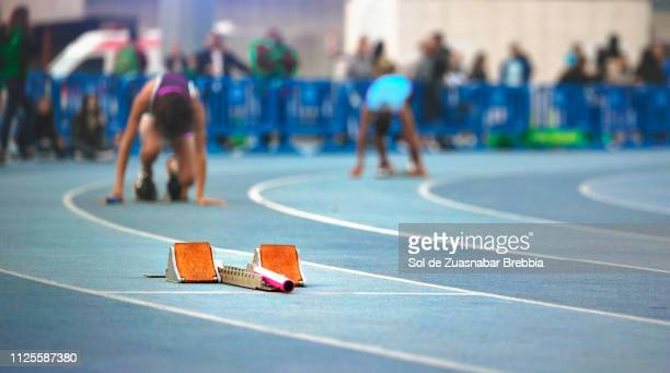 Close up of a starting blocks on a track and field with athletes and public behind