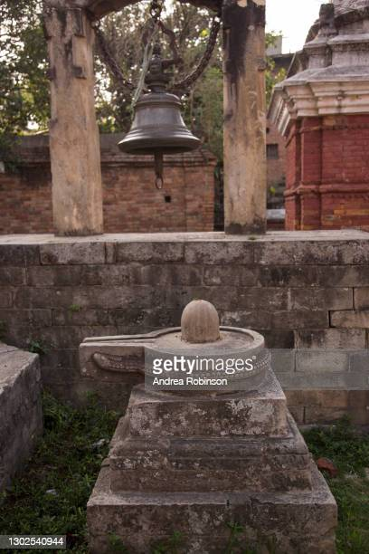 close up of a stone shiva lingam with bell alongside adjacent to the giant shiva lingam in the hanuman ghat area of bhaktapur in the kathmandu valley, nepal. - shiva lingam stock pictures, royalty-free photos & images