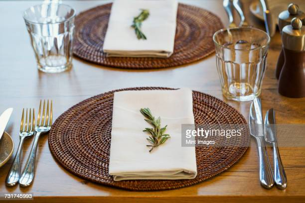 Close up of a table setting with place mat, napkin and cutlery at a hotel.