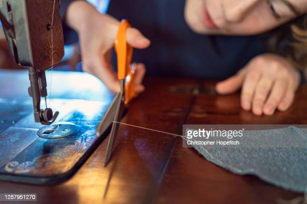 close up of a teenage boy cutting a thread while sewing at home - sewing stock pictures, royalty-free photos & images
