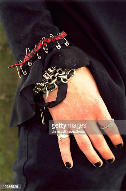 Close up of a teenage Goth's hand with chain and safetypin bracelets London UK 2003