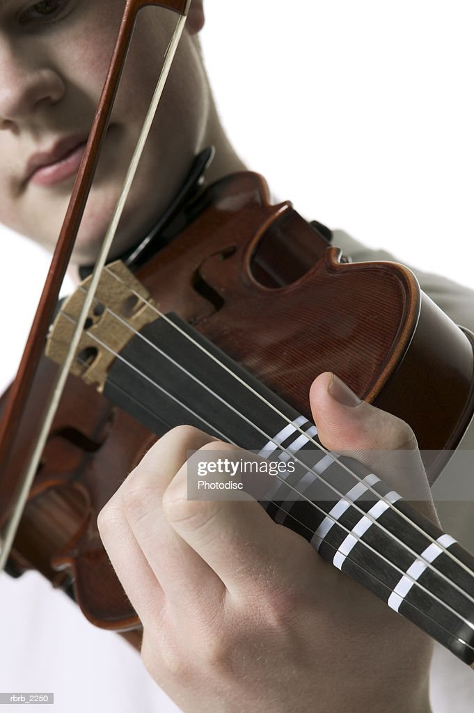 close up of a teenage male as he plays the violin : Foto de stock