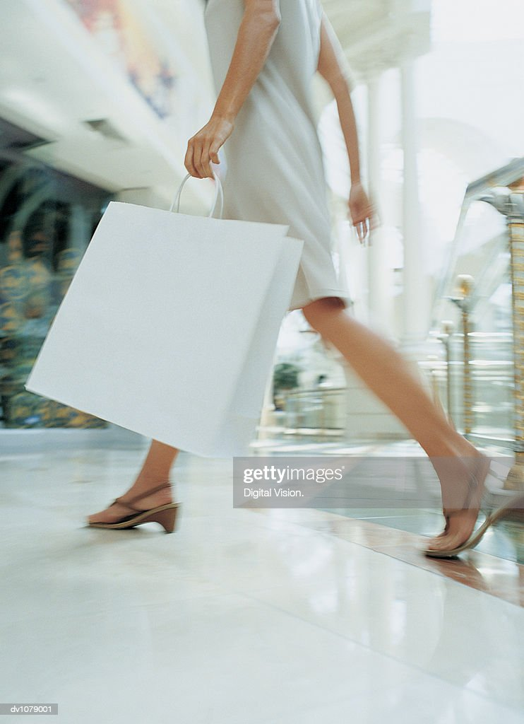 Close up of a the Legs of a Woman Walking Through a Shopping Mall Carrying a Shopping Bag : Bildbanksbilder
