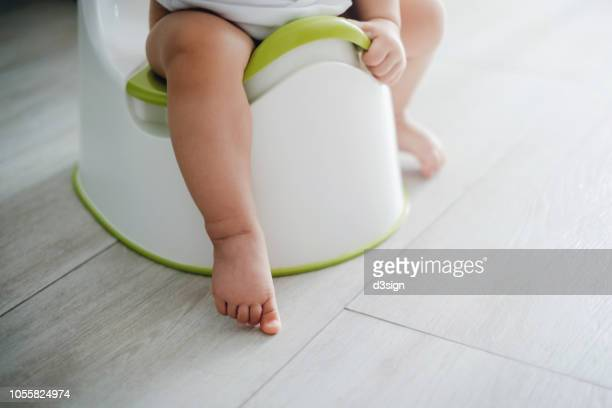 close up of a toddler sitting on a potty chair on potty training - babyhood stock pictures, royalty-free photos & images