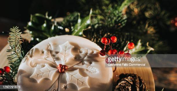 close up of a traditional luxury iced christmas fruit cake, decorated with holly, berries, fern and acorns. - bakery stock pictures, royalty-free photos & images