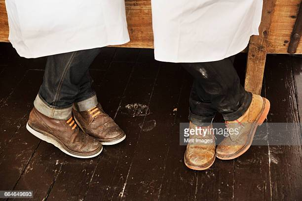 Close up of a two mens legs and feet, wearing white aprons, jeans and brown brogues with red shoe laces.