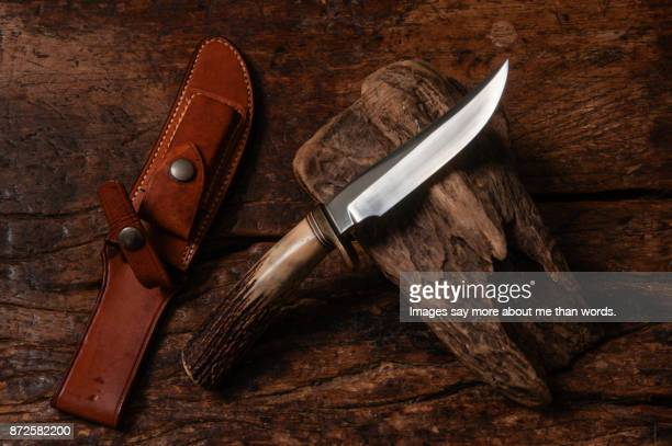 close up of a utility knife, its leather case and a wooden stump. - utility knife stock photos and pictures