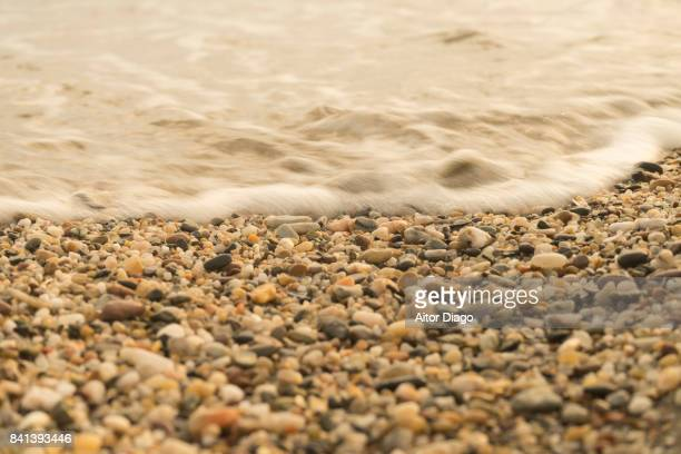 Close up of a wave covering small stones ashore.