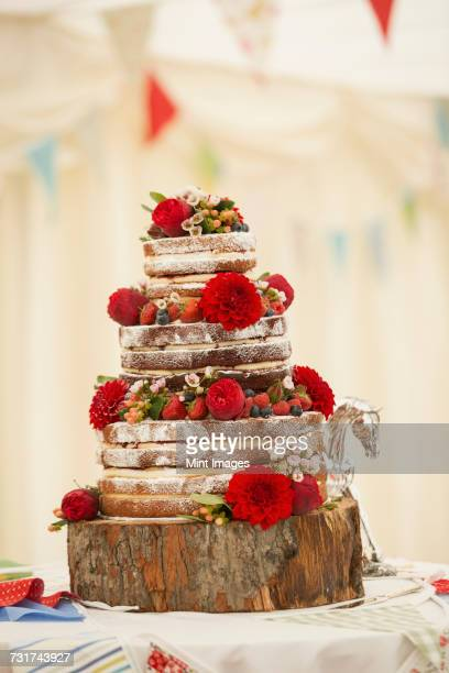Close up of a wedding cake decorated with strawberries and cream and fresh red flowers, dahlias set on a wooden log.