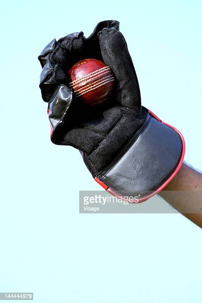Close up of a wicket keeper's glove and ball