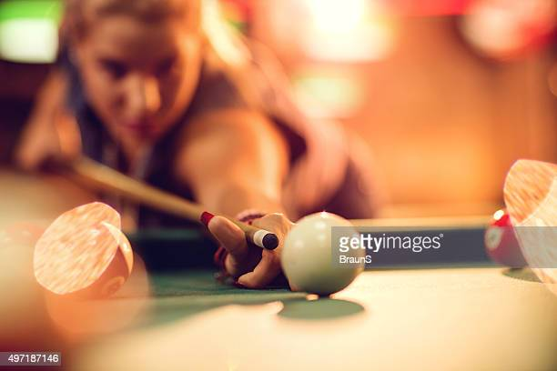 Close up of a woman aiming at pool ball.
