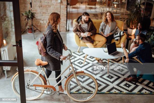 close up of a woman entering office with bicycle - millennial generation stock pictures, royalty-free photos & images