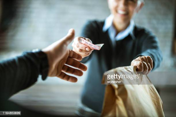 close up of a woman giving money to delivery person. - food delivery foto e immagini stock