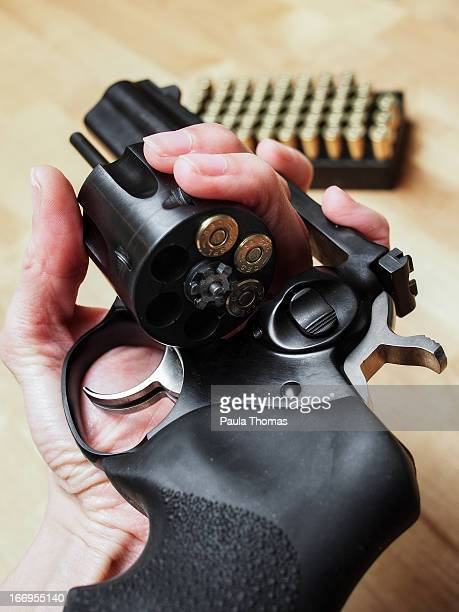 Close up of a woman holding a black revolver with the cylinder open, half loaded with 38 special ammunition.