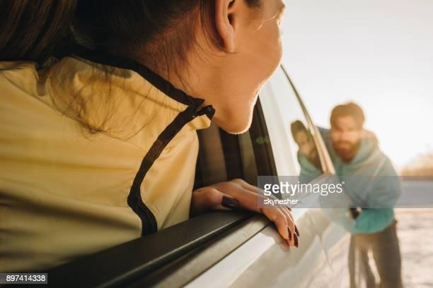 Nahaufnahme einer Frau in kaputten Auto Blick auf Männer, die ihr hilft.