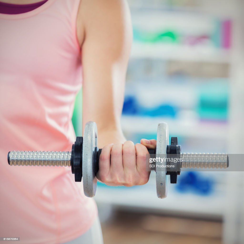 Close up of a woman lifting a dumbbell : Stock Photo