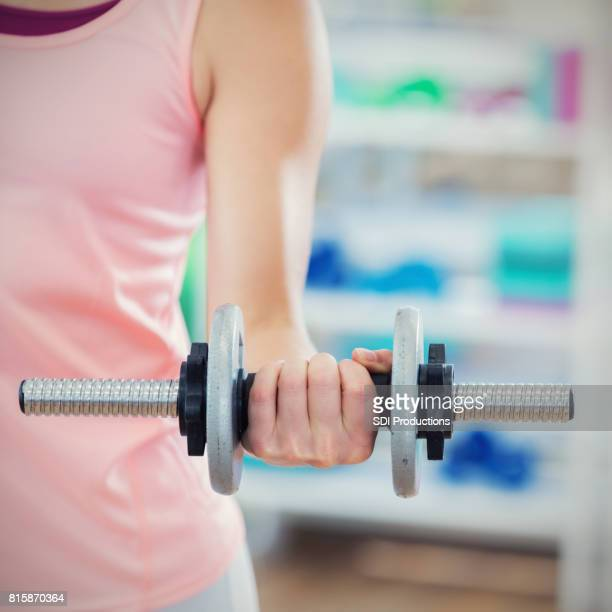 close up of a woman lifting a dumbbell - circuit training stock photos and pictures
